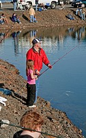 This Caucasian grandfather is helping his cute granddaughter to catch fish at a kid's fishing derby held at Banks Lake Washington on April 15, 2010 Ba...