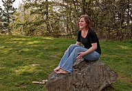 This image is a young Caucasian woman wearing blue jeans and a black shirt, laughing while sitting barefoot on a large rock Very natural looking, outd...