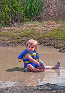 This cute 18 month old Caucasian toddler girl is sitting in her diaper and life vest in a mud puddle and playing as she's taking off her sandal Great ...