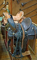 This veritcal image depicts two retro leather horse saddles, one brown and the other a light tan color, on sawhorses with various iron brands in the b...