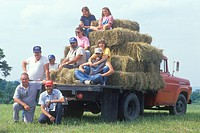 Family sitting in a flatbed with hay bales