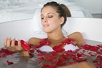 Woman enjoying a bath with petals