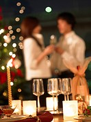 Wineglasses and candles on table, couple in background, differential focus