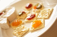 Plate of crackers with cream cheese and jam, close up, differential focus