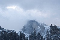 Half Dome stands amid the clouds in Yosemite Valley in winter.