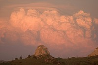Clouds forming over buttes reflect the sunset in the Grasslands.