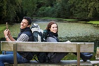 portrait of backpack couple sitting back to back on bench, next to lake