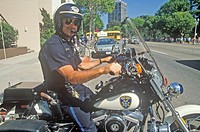 Oakland policeman poses on his motorcycle in Oakland, California