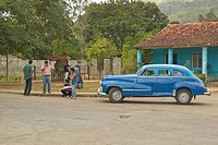 Old cars and three people in Cuban village in rural central Cuba
