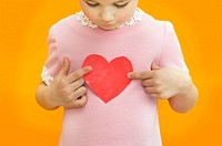 girl in pink dress holding heart shape