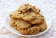 Broken raisin oatmeal cooky on pile of cookies.