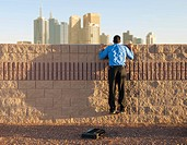 Businessman Looking over Wall at City