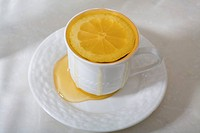 A cup of honey and a lemon slice