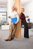 Two people standing between office doors