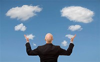 Businessman and comment bubble shaped clouds