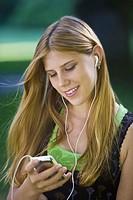 Teen girl enjoying her mp3 player outdoors