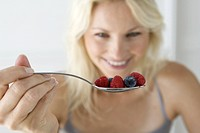 Woman eating bowl of fruit, focus on spoon