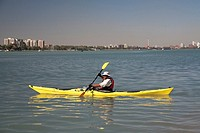 Detroit, Michigan - A man paddles a wooden kayak in the Detroit River