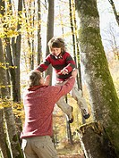 Mature man catching son leaping from tree in autumn forest