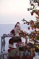 Mid adult man dressed as Santa Claus sitting at desk next to Christmas tree