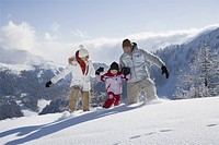 Family walking through deep snow on ski slope