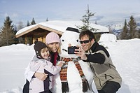 Mid adult man taking photograph of family with snowman