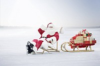 Senior man dressed as Santa Claus sitting on chair by sled full of presents