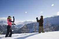 Mid adult couple throwing snowball to each other, side view