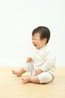 Baby boy crying against white background