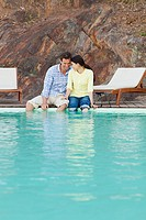 Mid adult couple sitting at poolside with legs dangling in water (thumbnail)