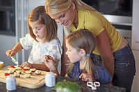Mother and her daughters making finger food together