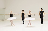 A group of young male and female ballet dancers practicing