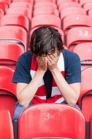 Disappointed football fan in empty stadium