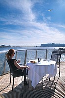 Young woman enjoying lunch and wine at the St Davids hotel, Cardiff bay, South Wales
