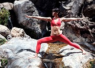 Yoga poses in front of water creek.