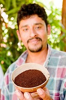 Farmer showcasing his coffee in a coconut shell