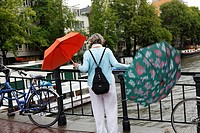 Which umbrella will she use, streetscenes of Amsterdam during a rainy day, Netherlands
