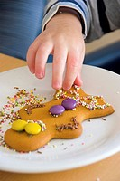 A young child reaches for a decorated gingerbread man cookie