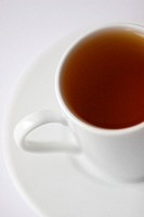A white cup of black rooibos tea rests on a saucer against a white background