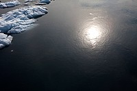 the sun reflects off the sea amidst icebergs from an overhead view