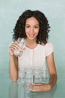 Young woman holding a glass of water with seven glasses of fresh water on a glass table