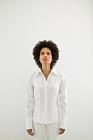 Woman looking up wearing all white on white background.