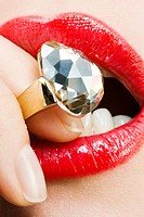 Woman biting on diamond ring, close_up