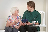 Male carer & elderly woman looking at photographs