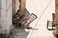 A traveling, itinerant, worker repairing rush seated chairs in the village of Proastio, near Kardamili in the outer Mani, Southern Peloponnese, Greece