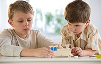 Two young boys building a wooden train