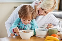 Mother and daughter having breakfast in kitchen