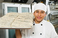 Chef holding tray of bread