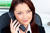 Assertive young businesswoman talking on phone smiling at the camera in her office