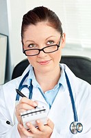Thoughtful female doctor smiling at the camera holding a notepad in her office sitting at her desk